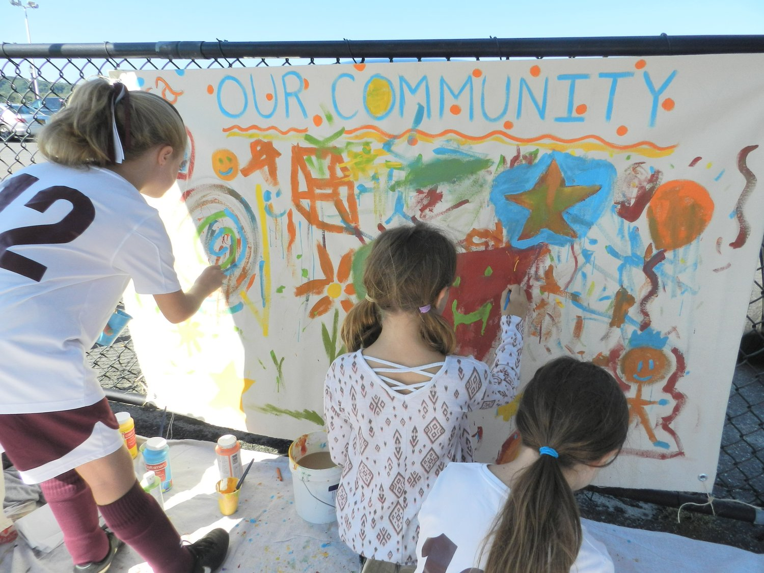 Glenwood Landing students Hailey Colbert, left, and Juliet and Abigail Monte contributed to NSCASA's community art mural.