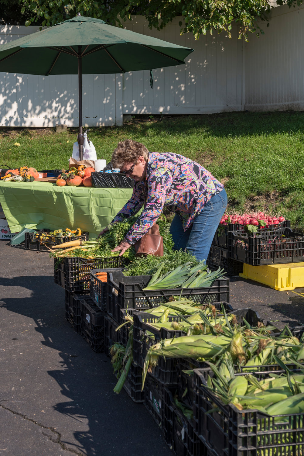 Irena Debiec neatly arranged corn, carrots and other locally grown produce before buyers came to market.