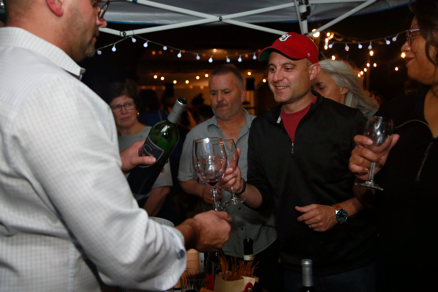 Chris Parra, left, provided wine for many residents, including Robert Drysielski at Crossroads Farm's annual wine tasting fundraiser on Sept. 21.