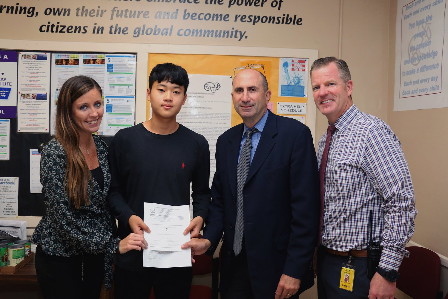 West Hempstead High School guidance counselor Jacqueline Lennon, left, presented senior Theodore Kim with a letter of recognition as a Commended Student in the National Merit Scholarship Program. Kim was joined by WHHS Principal James DeTommaso, second from right, and Assistant Principal Adam Hopkins.