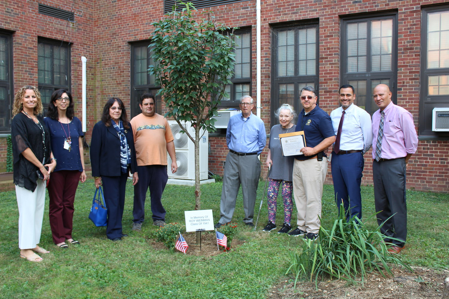 The Mepham High School community honored late Bellmore man-about-town Roy Weinman on Oct. 3 with a tree in the school's courtyard. Above, from left, were Mepham Assistant Principal Jennifer Carne, Leo Club adviser and Lion Josephine Parlagreco, Lions Michelle Gagnone and Jack Skelly, Myrna Weinman, Lions Club member John Scalesi, Mepham Principal Eric Gomez and Assistant Principal Andrew Del Rosario.
