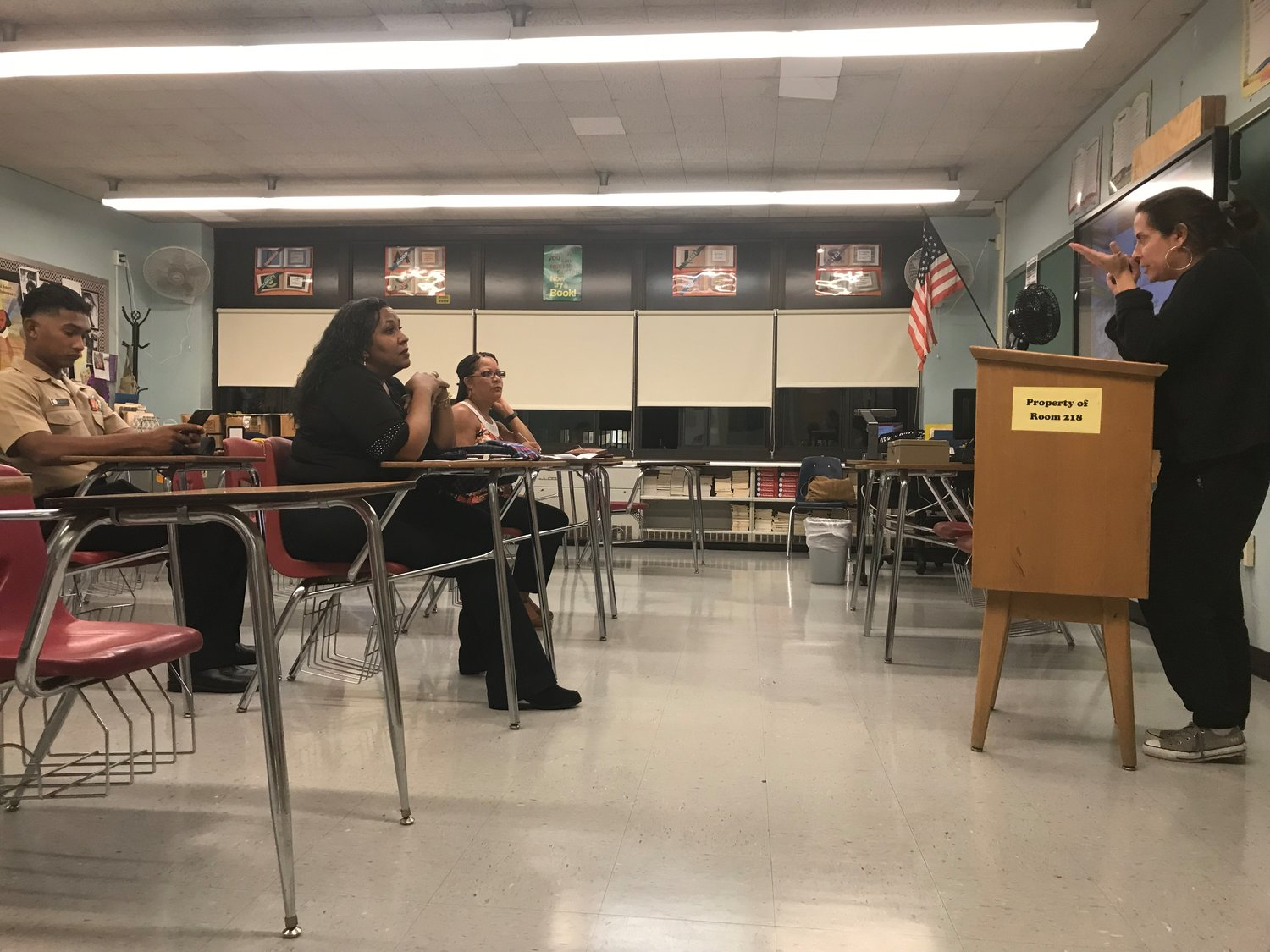 Hispanic parents sat at their children's desks while meeting with Pam Yodowitz, an 11th grade English teacher at Freeport High.
