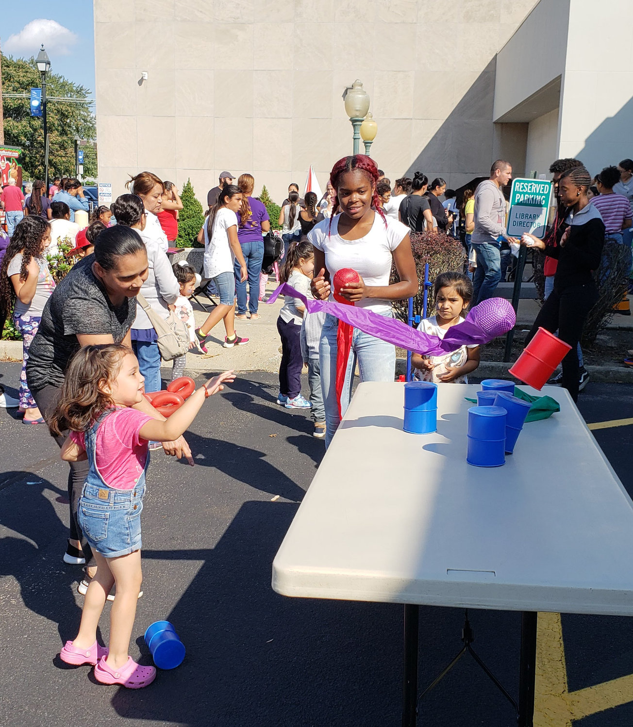 In an effort to knock down the cans to win a prize, Samantha Diaz Mendoza, 4, threw a purple ball with the help of her mom, Ruth Mendoza, left, while Freeport High School volunteer, Kayla Dwyer, 17, looked on.