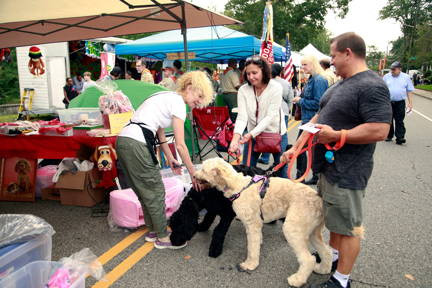 Maria and Bill Sonner, right, brought their golden doodles, Alvin and Simone, out to West Hempstead's annual Street Fair as they met with Sherry Bishop on Oct. 7.