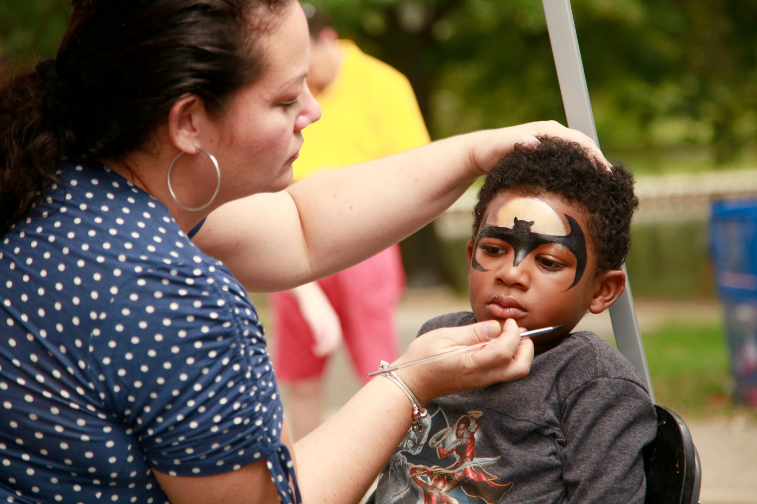 Natalie Hernandez painted a batman symbol on Elijah Sargeant, 4.