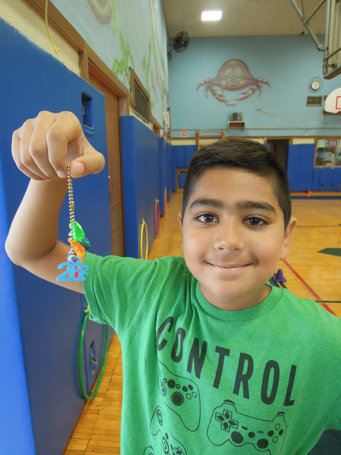 "Fifth grader Sami Shaikh showed his ""toe tokens."" Tokens are given for teh first mile and for every five miles after. Sami's ""26"" token indicated that he had run a marathon with family members."