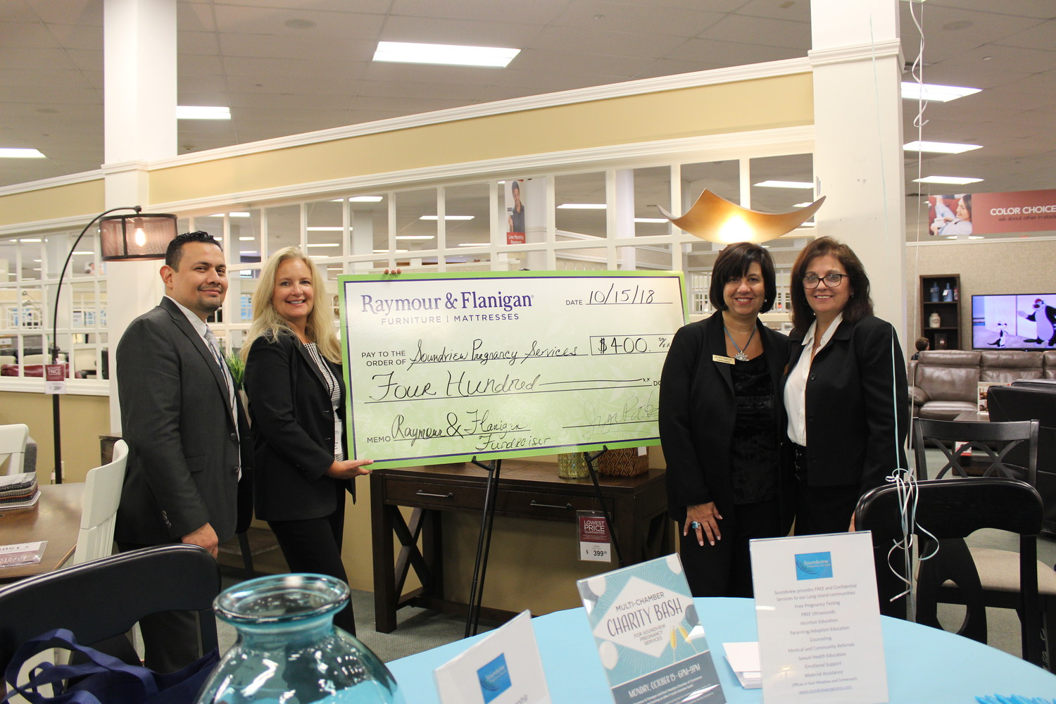 Christine Mooney, the vice president of the East Meadow Chamber of Commerce, far-right, joined with Juan Ruiz, left, and Michele Giaccio, right, both showroom managers at Raymour and Flanagan, to give a check for $400 to Julie Fehring, the director of development at Soundview Pregnancy Services.