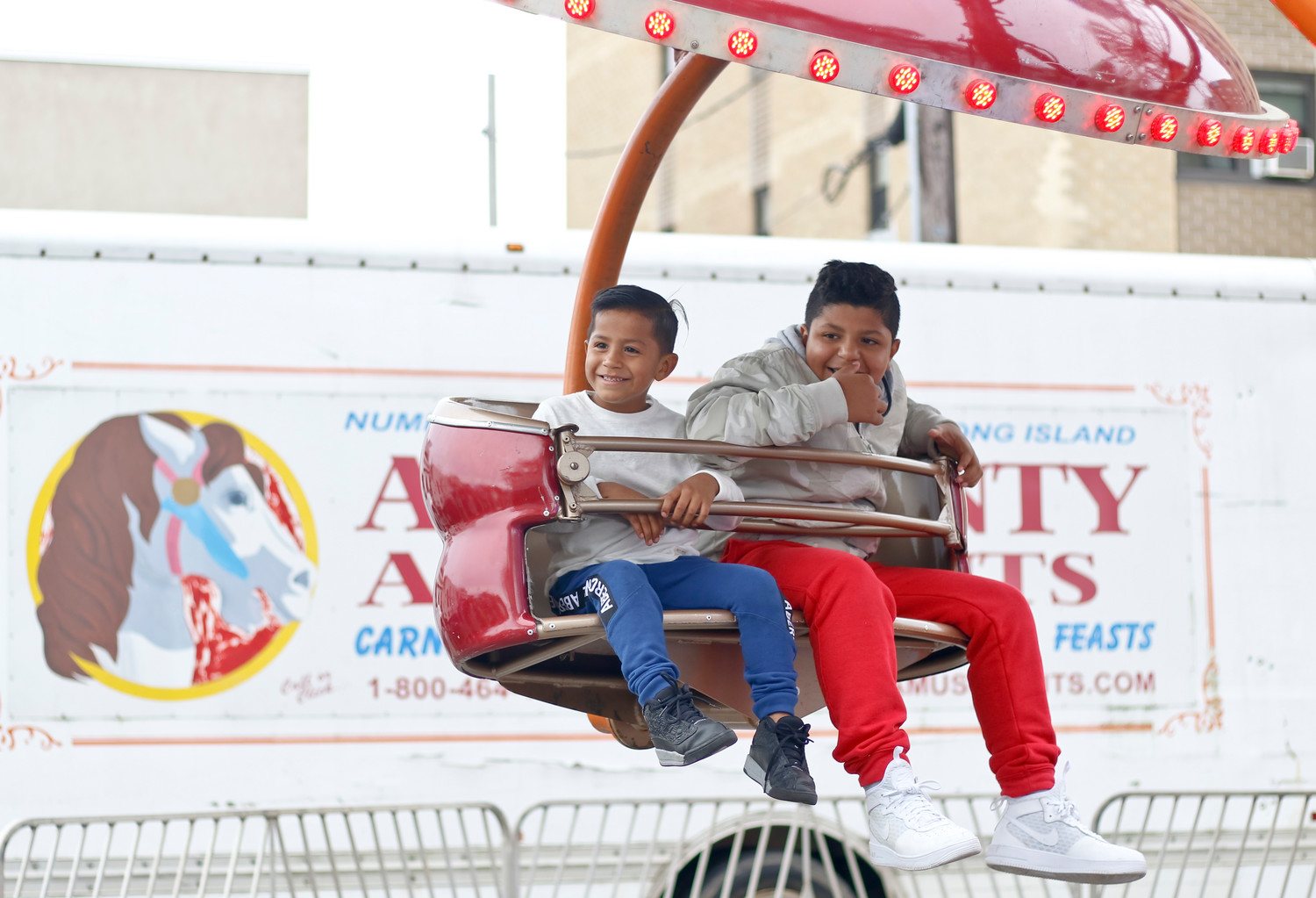 Brothers William Carballo, 5, and Freddy Rivera, 11, rode the flying saucer ride at the city's annual Fall Festival in Kennedy Plaza on Saturday.