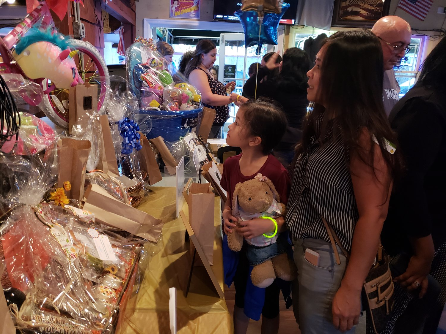 Nine-year-old Danielle Guerrera, from Levittown, checked out the raffle prizes with her mother, Cindy, at the fundraiser at Jeremy's on Oct. 9.