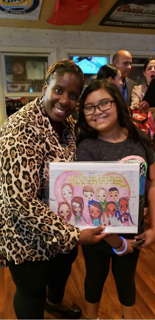 Lisa Baptiste, left, smiled after Laiyla Salome-Diaz presented her with a picture she drew for Taliyah and submitted to the Shanti Art contest.