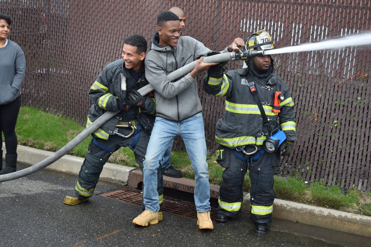 Elmont Memorial High School student Marven Bernard, 17, tried out one of truck's hoses with the help of Engine Company 704 Capt. Lamar Kelly, right, and Engine 4 volunteer firefighter Richard Baker.