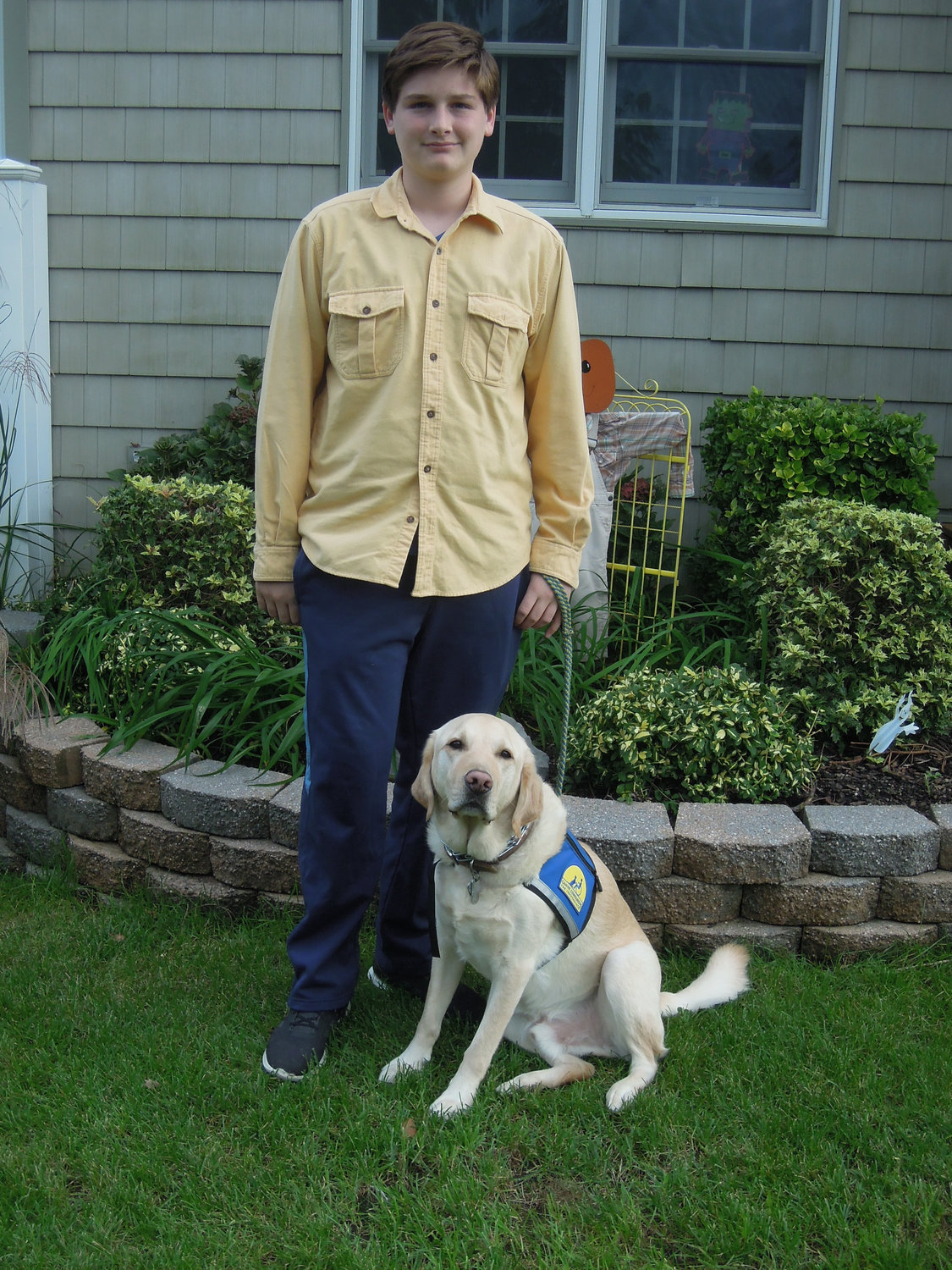 Luke Tordy with his service dog, Dragon, outside their Wantagh home.