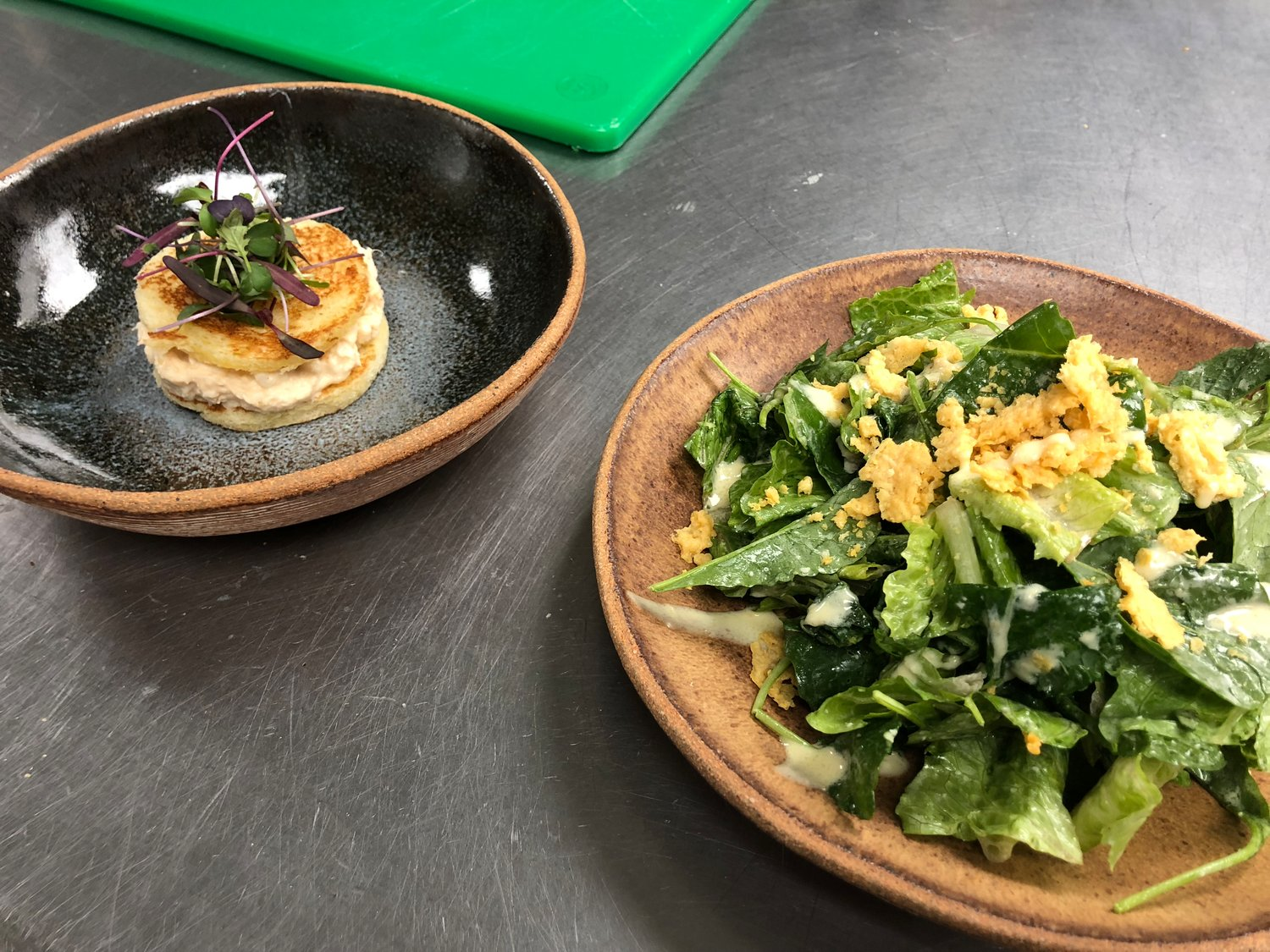 Two of Maldon & Mignonette's seasonal appetizers: crab cake with garlic soubise, left, and kale Caesar salad.
