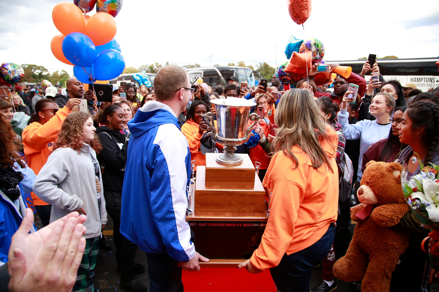 Band directors Glen Johnson and Alyssa Rizzuto carried the trophy through the crowd at Malverne High School.