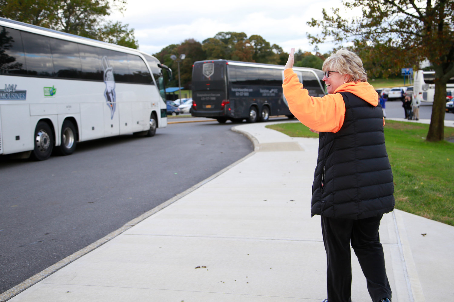 Malverne Mayor Patti Ann McDonald waved to the marching band as they arrived on the buses.