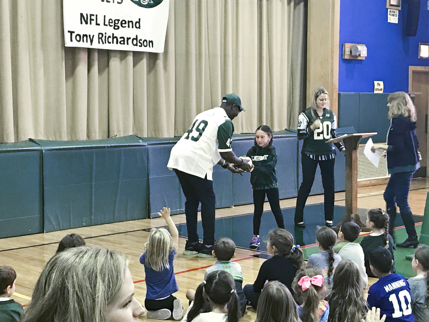 Fourth-grader Zoe Garver received a signed football from former Jets fullback Tony Richardson for correctly answering a question based on the health and wellness lessons students learned at Waverly Park School.