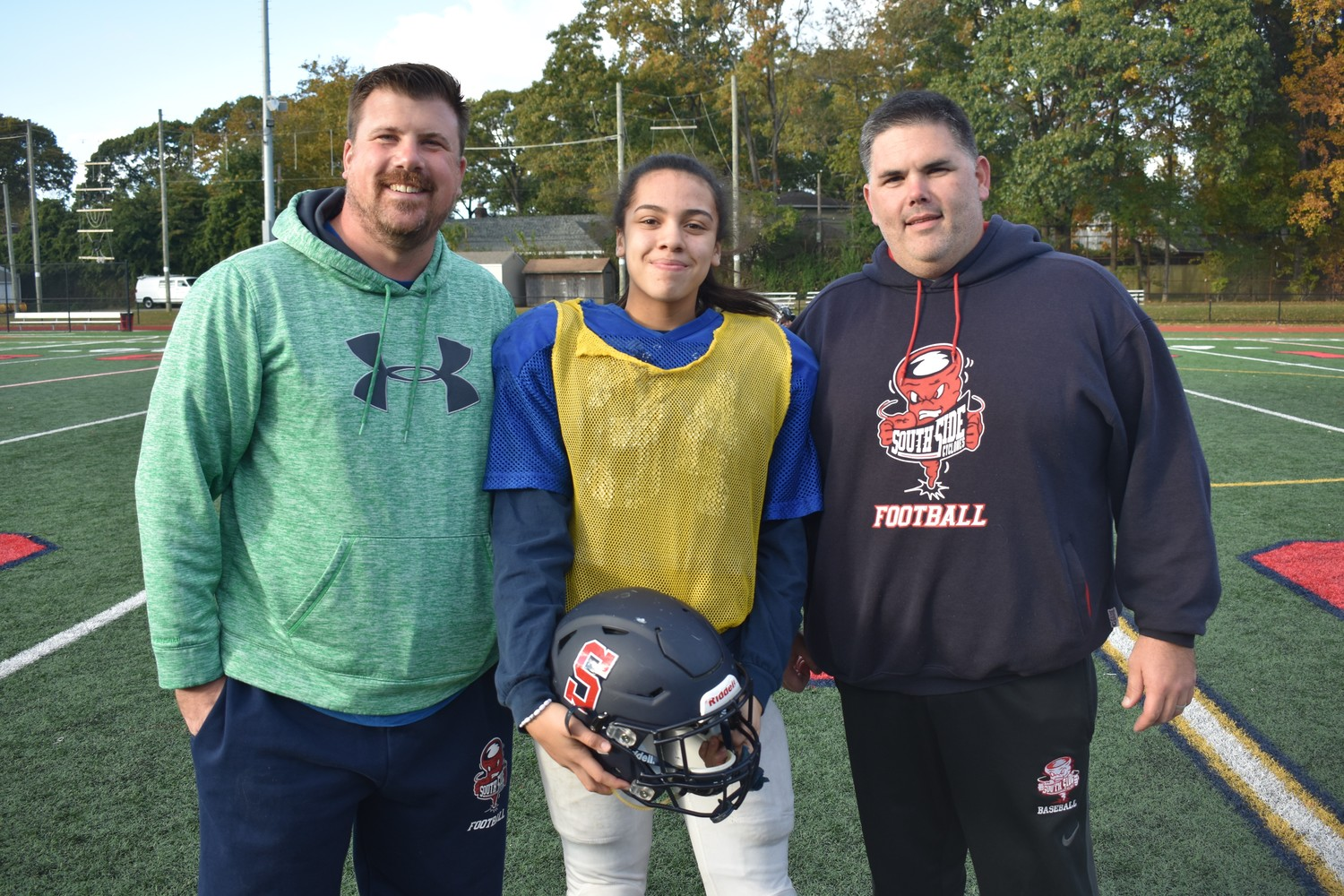 Olivia Medford, with junior varsity co-coaches Keith Bosch, left, and Thomas Smith, who welcomed her to the squad last year.