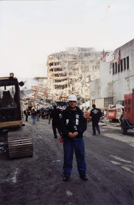 Hanlon in 2001 standing near debris from the Sept. 11 terrorist attacks.
