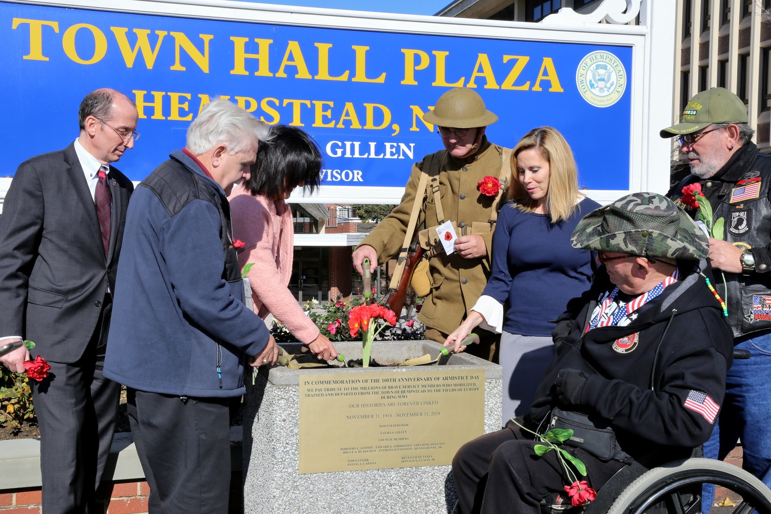 Gary Port, the United States army reserve ambassador to New York State, left, Ralph Esposito, the director of the Nassau County Veteran Service Agency, Sylvia Cabana, the Town of Hempstead clerk, Peter Bugala, a World War I reenactor, Laura Gillen, the supervisor of the Town of Hempstead, Andy Booth, the former commander of the Nassau County American Legion and Sal Martella, a member of the American Legion Post 1848 celebrated Armistice Day by planting red poppy seeds in a flowerbed at Hempstead Town Hall. The flower is a symbol of remembrance for those lost during World War I.
