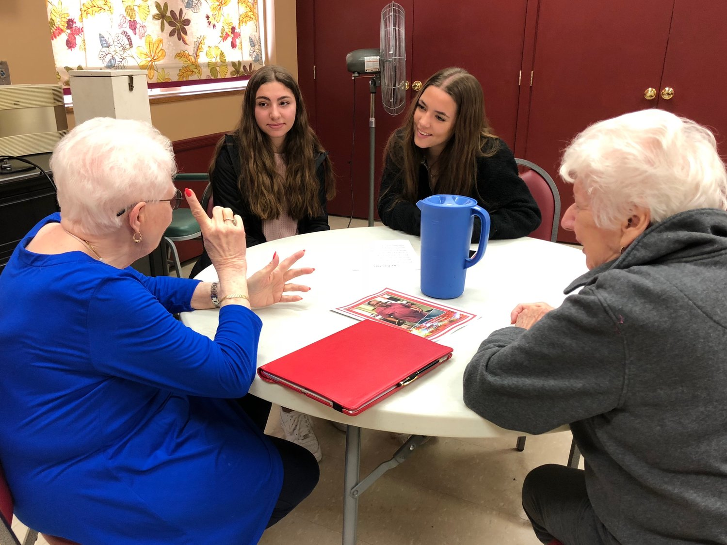 Sally DiMiceli, left, and Mimi Simonetti spoke with Friends Academy students Anastasia Kazanas and Ally Grella at an intergenerational program at the Glen Cove Senior Center.