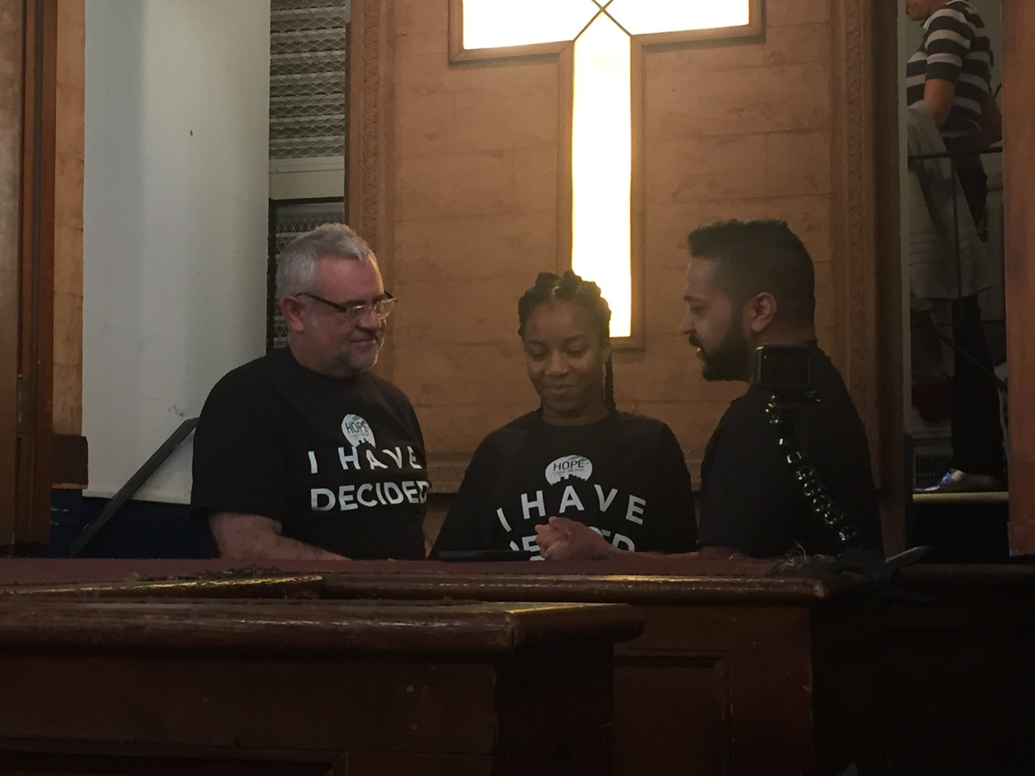 Hope Church Long Island staged its first-ever baptismal service on Oct. 28, two years after its official launch as a church plant. Santiago Bernal, left, and Pastor Finn Varughese, right, prepared to immerse Hofstra student Olukemi Anazodo after she professed her faith in front of the congregation.