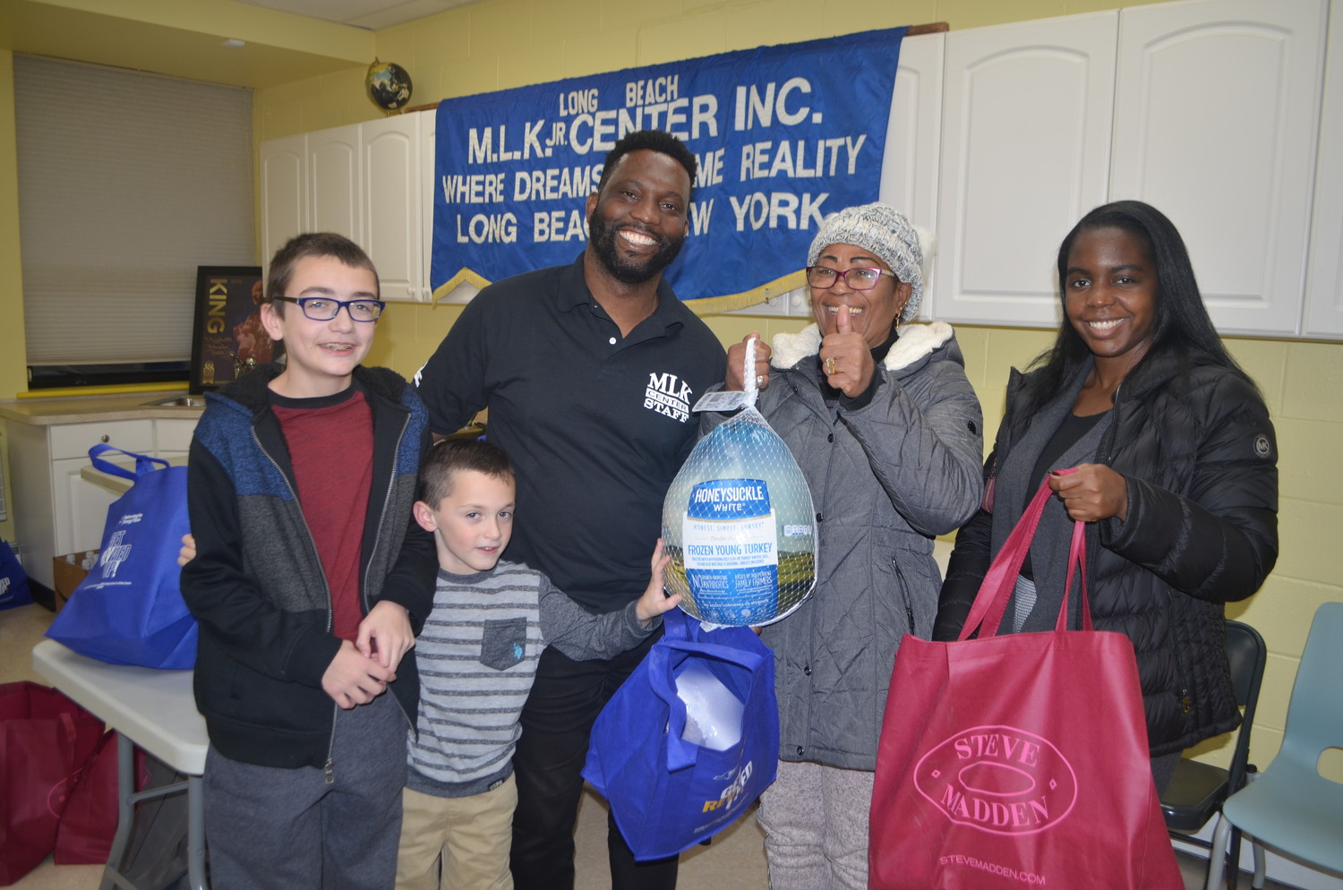 Jacob Hurney, left, Luke Santeramo, Martin Luther King Center board Chairman James Hodge, and Andrea Wilkins, far right, handed a turkey and a bag of traditional Thanksgiving dinner trimmings to Long Beach resident Milagro Rodriguez on Tuesday.