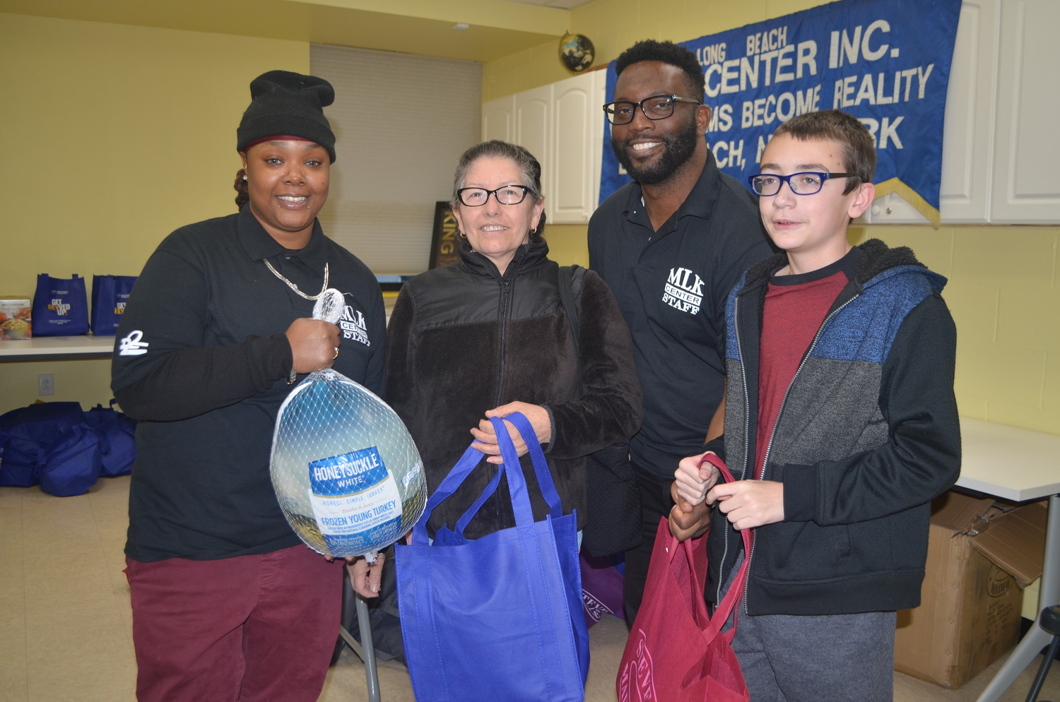 Nyasia Hurd, left, Hodge and Jacob Hurney, far right, handed a turkey and dinner trimmings to Norma Castro.