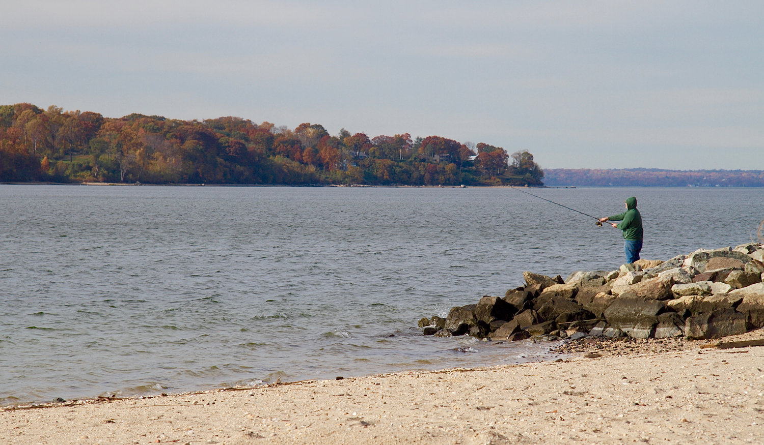 A lone fisherman throws his line into Hempstead Harbor from the shores of Sea Cliff Beach, hoping for one last catch.