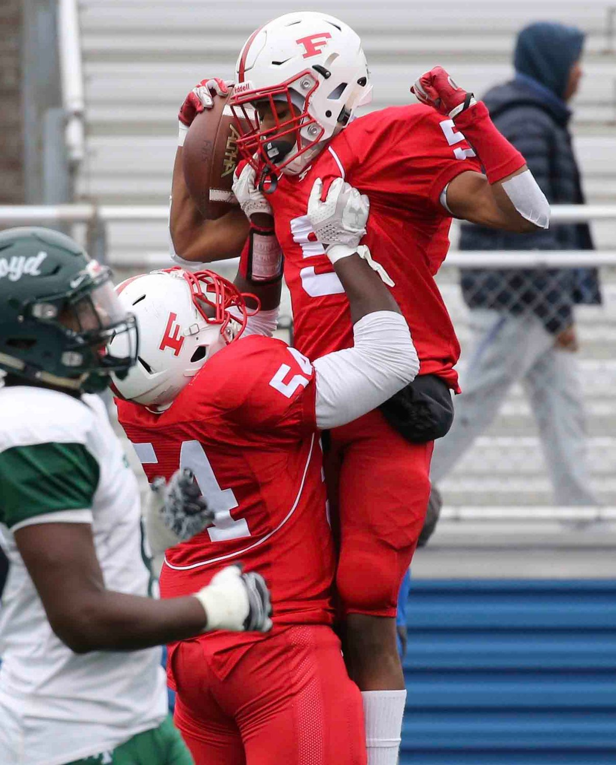 Freeport's Jordan Jackson, right, got a lift from Gerard Smikle after he opened the scoring in Saturday's 20-19 victory over William Floyd in the Long Island Class I championship game at Hofstra.