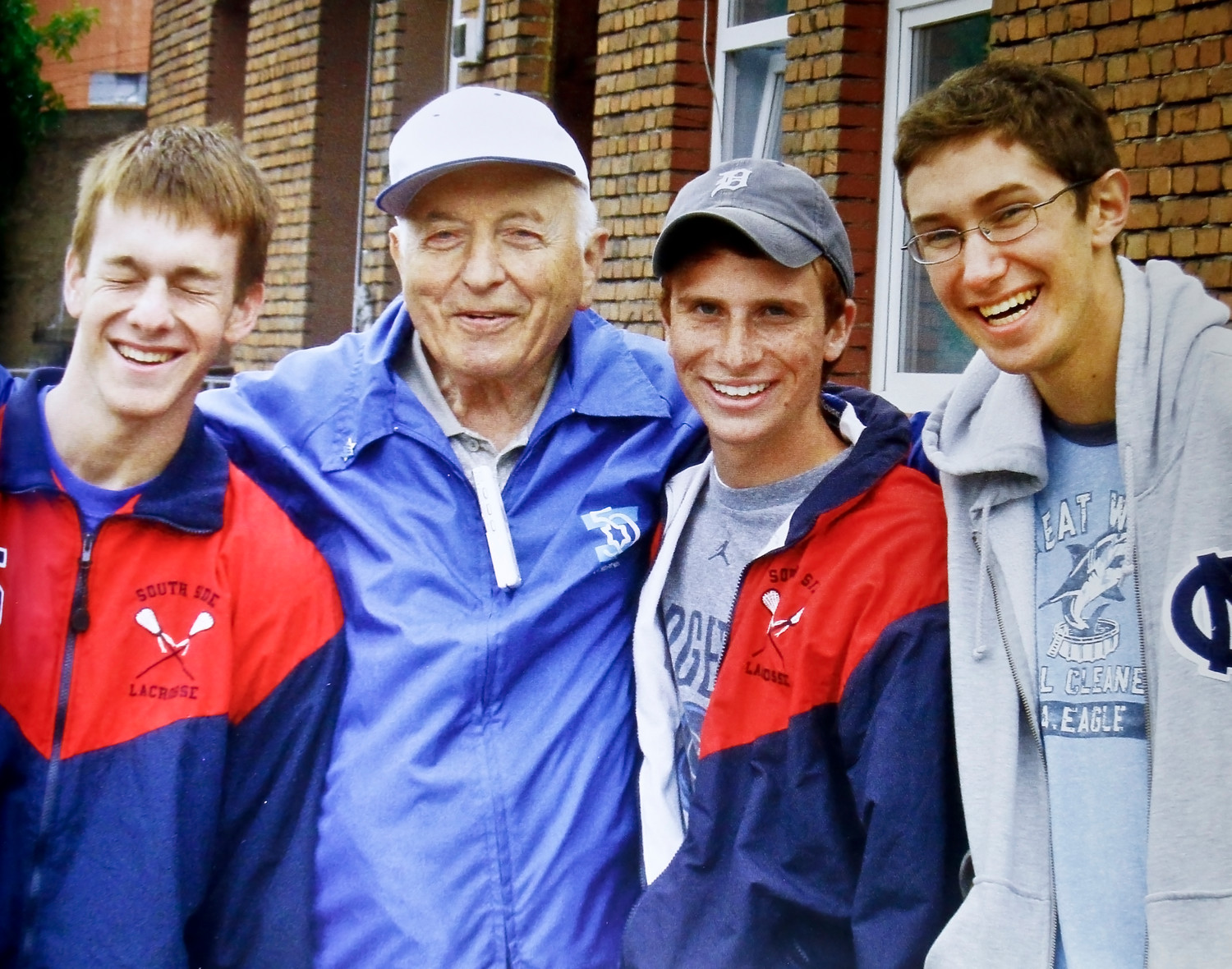 Ray Fishler visited Poland with three Rockville Centre families in 2007. Michael Heller, far left, Lucas Richner and Zachary Mandinach joined him outside his former home in Kazimierza Wielka, Poland.