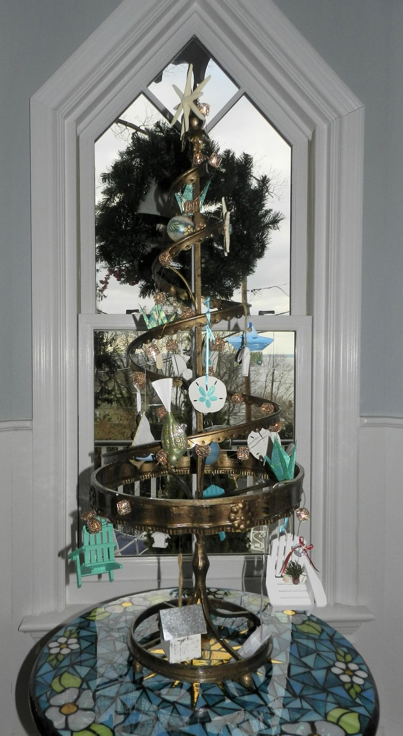 In Jane McGilloway's seaside cottage, a bronze Christmas tree is dressed up with seashells, beach chairs and starfish.