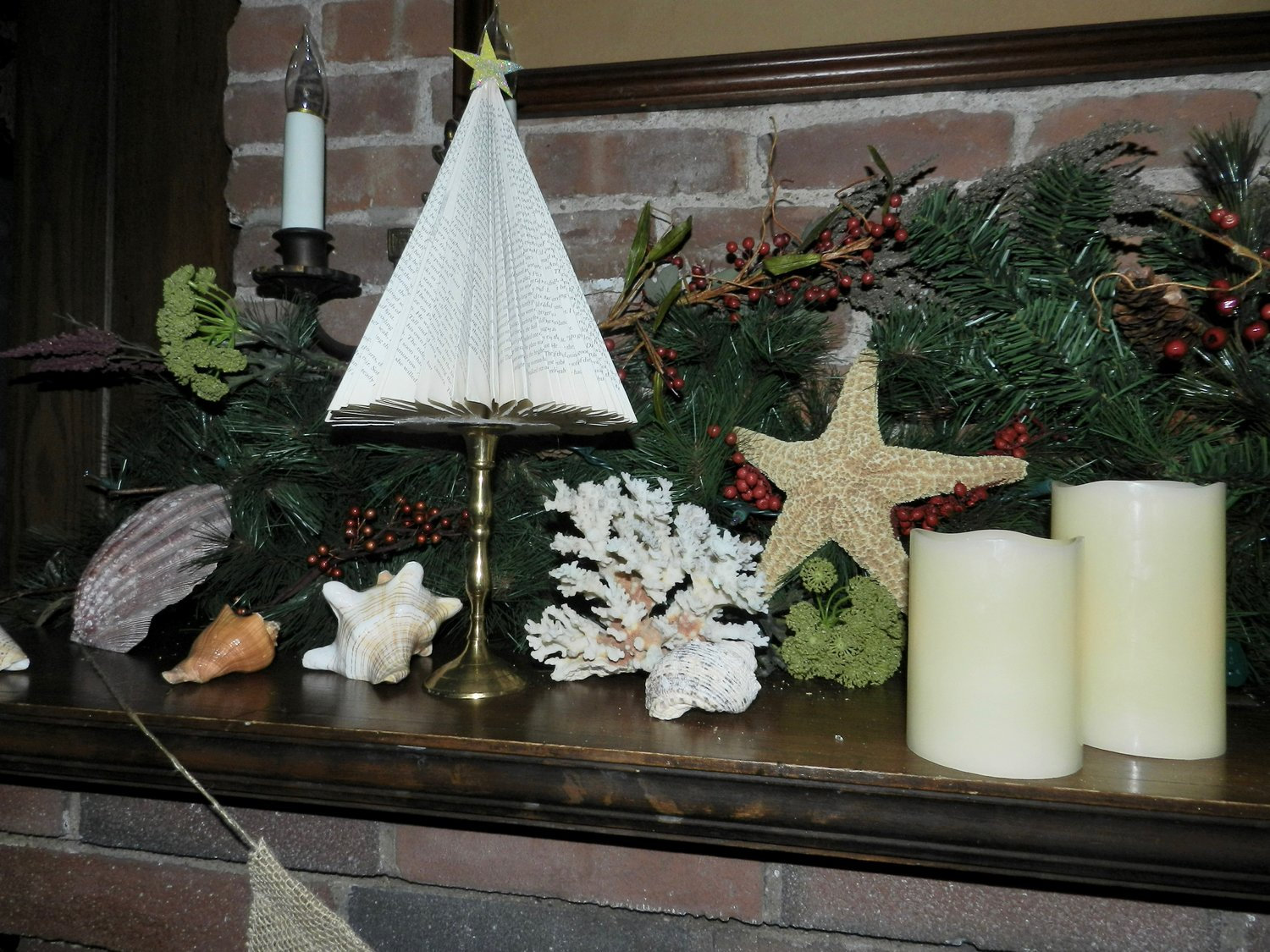 Como's mantel features touches of marine life, festive greens and a miniature tree crafted from the pages of a book.