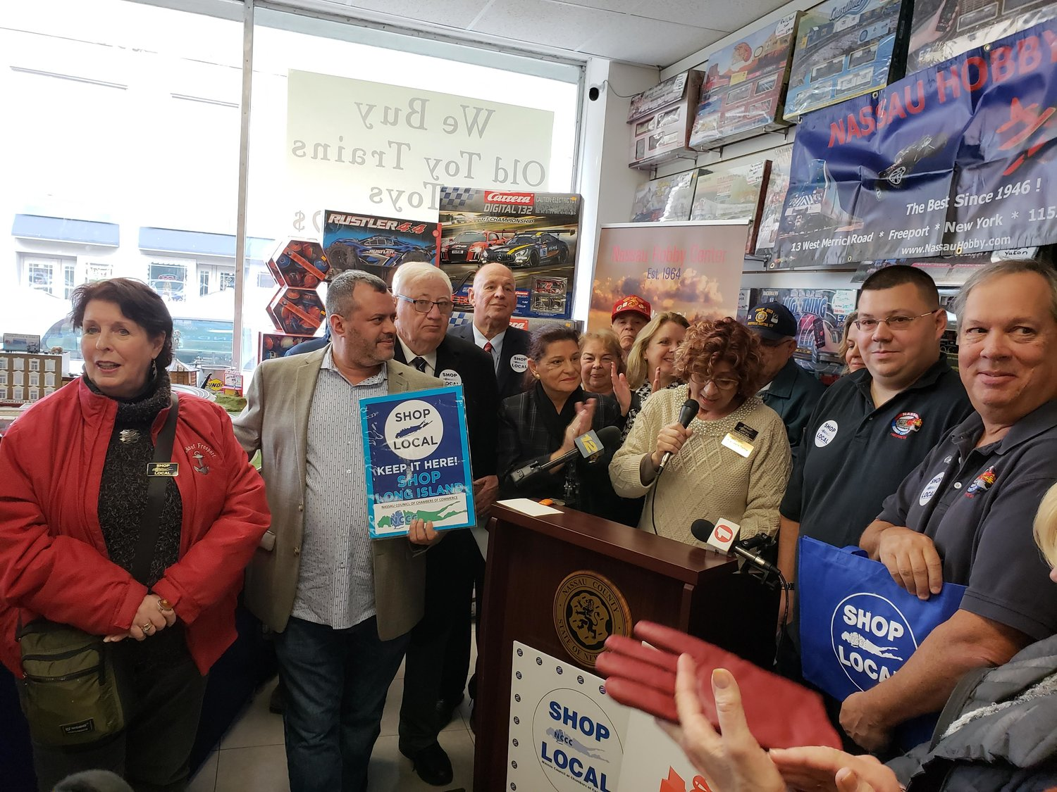 "Francesca Carlow, president of the Nassau Council of Chambers of Commerce, center, announced a countywide initiative to encourage Long Islanders to ""Shop Local"" this holiday season."