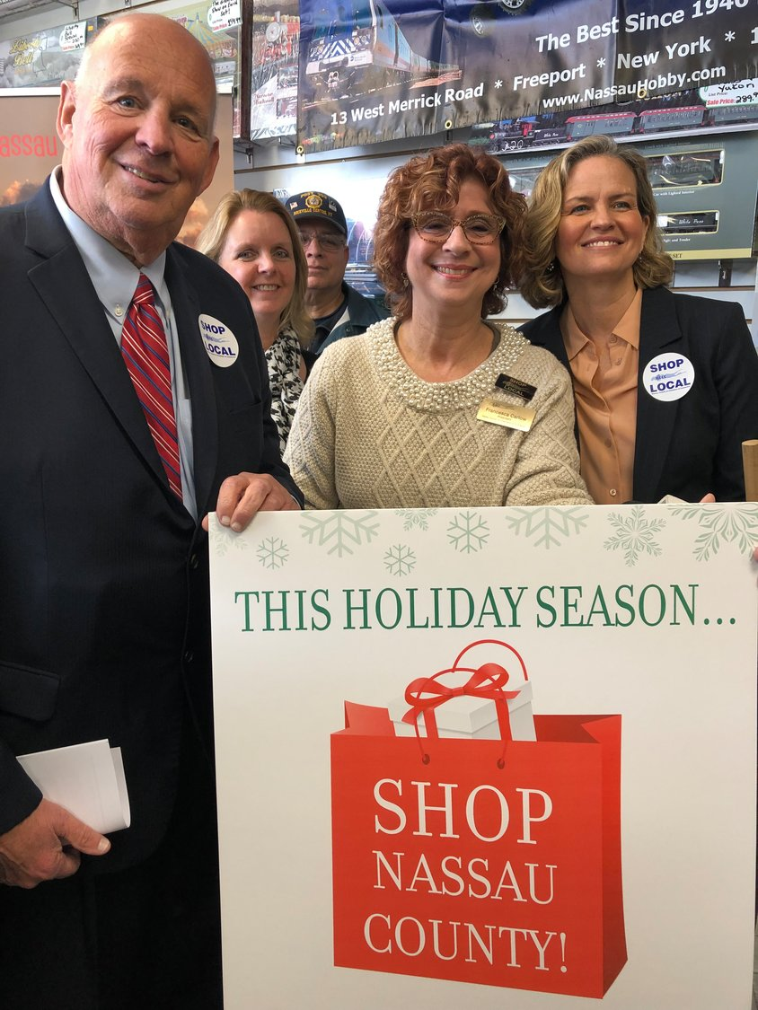 "Richard Kessel, chairman of the Nassau County Industrial Development Agency; Debra Mulé, Nassau County legislator; Francesca Carlow, president of the Nassau Council of Chambers of Commerce; and Laura Curran, Nassau County executive, held up a sign announcing the new ""Shop Local"" campaign at the Hobby Center in Freeport."