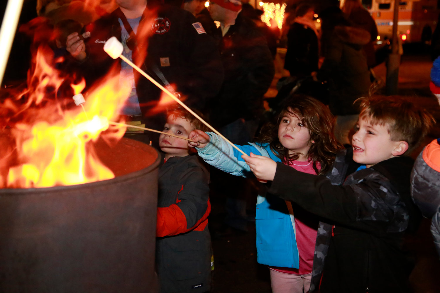 Henry, 6, left, Alex, 5, and Charlie LaSpina, 5, toasted marshmallows — one of many traditions at Malverne's annual tree-lighting ceremony — last Saturday.