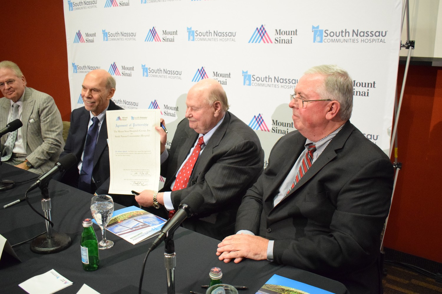 Representatives of South Nassau Communities Hospital and the Mount Sinai Health System announced their partnership Tuesday. Joseph Fennessy, the chairman of SNCH's board of directors, held the ceremonial agreement that was signed. WIth him, from left, were Mount Sinai President Dr. Arthur Klein, Mount Sinai CEO Dr. Kenneth Davis and South Nassau President and CEO Richard Murphy.