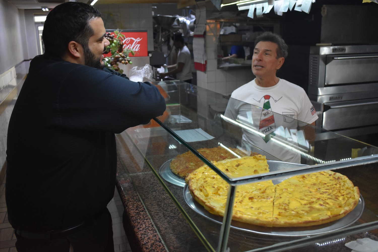 "Luca Miceli, owner of Mr. Miceli Pizza, above, chatted with customer Joel Fernandez a day before Miceli closed his shop. ""It was a pleasure,"" Fernandez told him with a handshake before leaving."