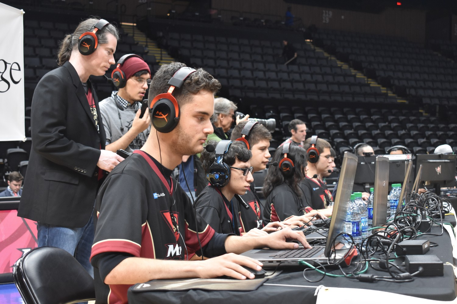 Molloy students Steven Rizzo, closest, Matt Nori, James Branker, Nina Barcelon, Will Keller and Andrew Gavalas competed played Overwatch against gamers from NYIT at the Nassau Veterans Memorial Coliseum on Dec. 2. Consultants Kerry Bourgoine, back left, and David Constantino, looked on.