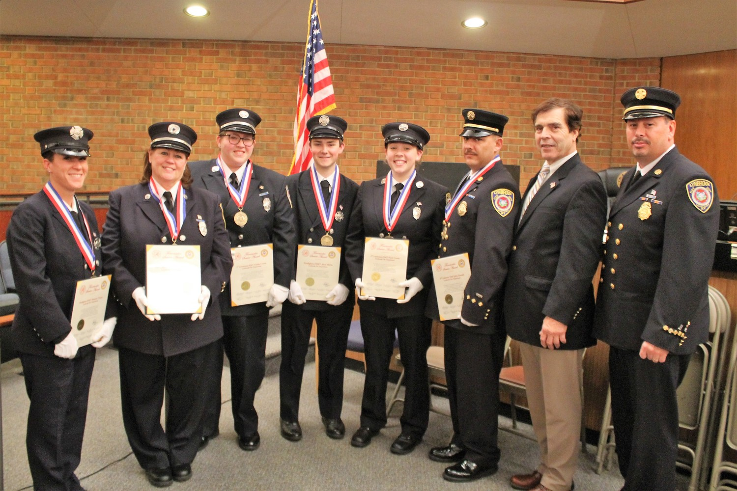 Six Lynbrook firefighters were honored by Hempstead Town Supervisor Laura Gillen for saving a Lynbrook woman's life in April. Above, from left, EMT Shannon Tracey, former Captain/EMT Cathy Bien, First Lieutenant/ EMT Kaitlyn Curran, Firefighter/EMT Alex Mertz, Second Lieutenant/EMT Kacie Curran, and Lynbrook Fire Department Third Assistant Chief John Donald with, from right, LFD Chief William Abrams, and Lynbrook Mayor Alan Beach.