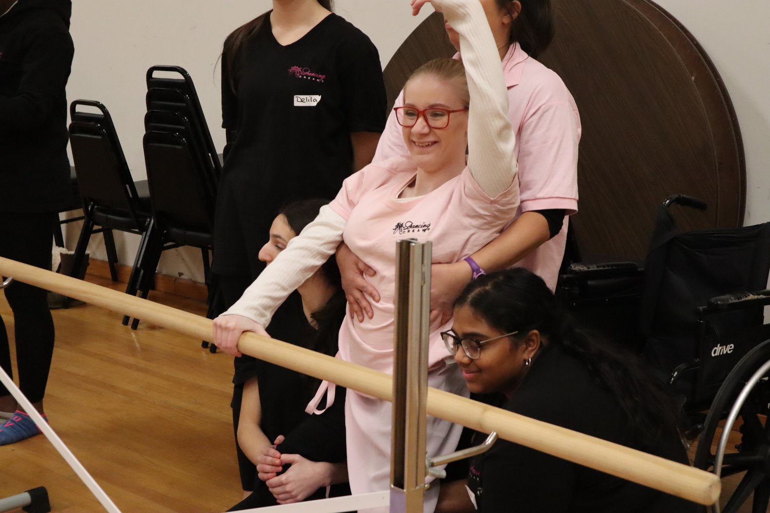 Abigail Penny, a young Merokean with spina bifida, expresses her movements through her arms while holding the barre.