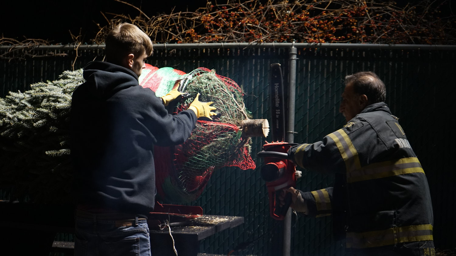 Firefighters Sean McBride, left, and Ronny Mastrangelo readied a tree for sale.