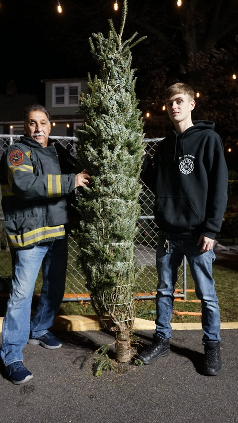 Mastrangelo and McBride with one of the larger trees they have available. The trees run from three to eight feet in height.