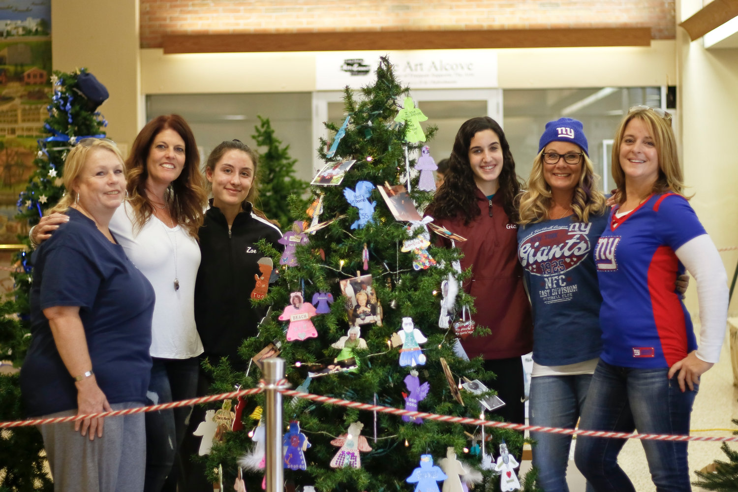 Decorators, from left, Mary Muldowney, Alicia Brodsky, Zoe Dallaris, Gianna Brodsky, Penny Smith and Kim Labrador hung ornaments memorializing those who have passed on. Under the tree is a basket of angels that people can decorate for a loved one they lost.