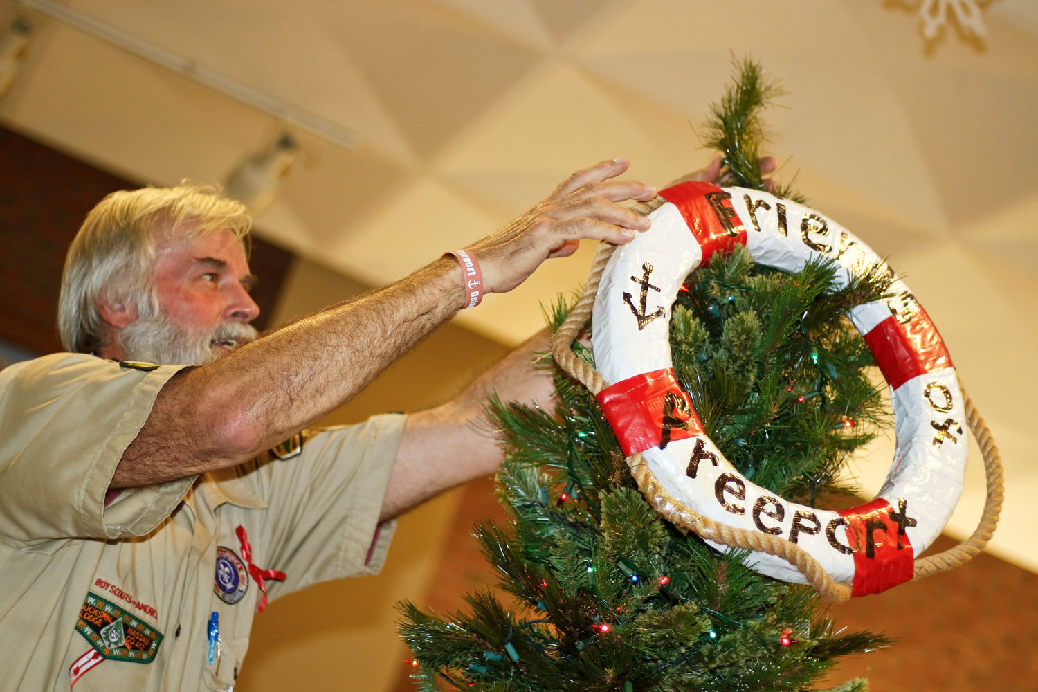 Friends of Freeport and Boy Scout Troop 36 leader Kurt Corelo helped decorate both trees but his height helped when topping the tree with a personalized life preserver.