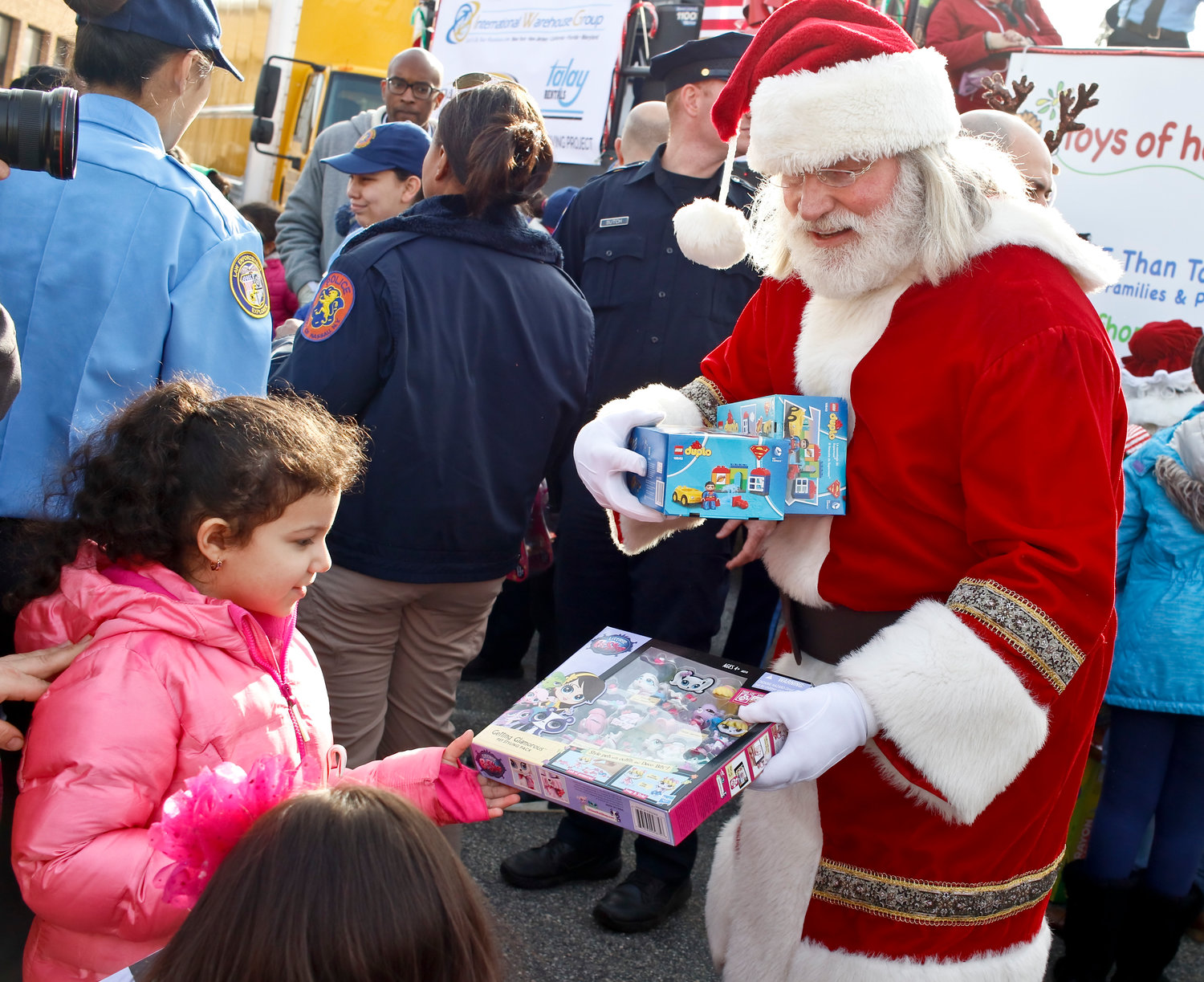 Santa Claus gave a Pet Shop set to Helen Salguero at the toys of hope event. Each child at the event received a toy.