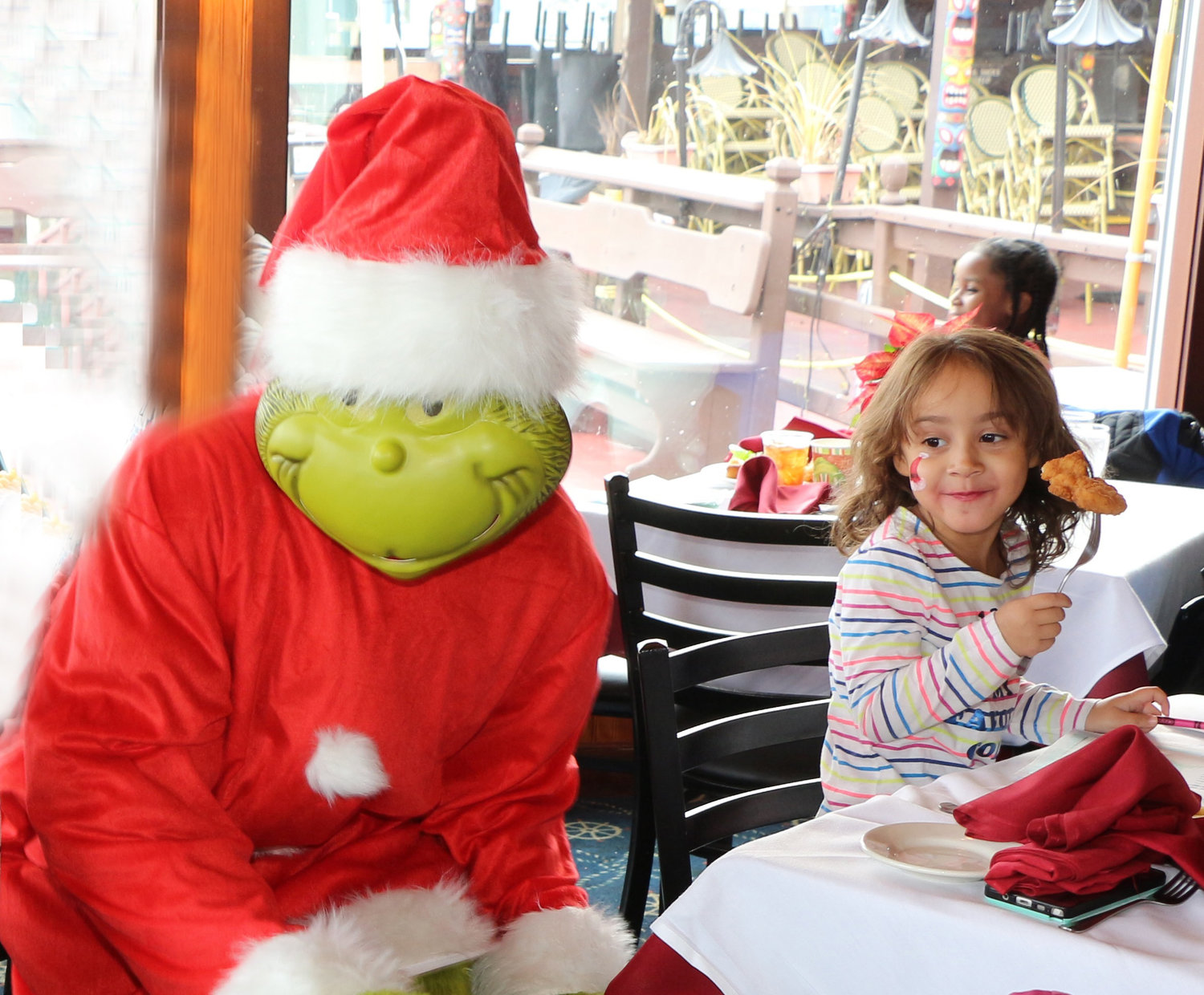 The Grinch sleeked his way around Otto's and surprised Abigail Bince, 4, while she ate lunch.