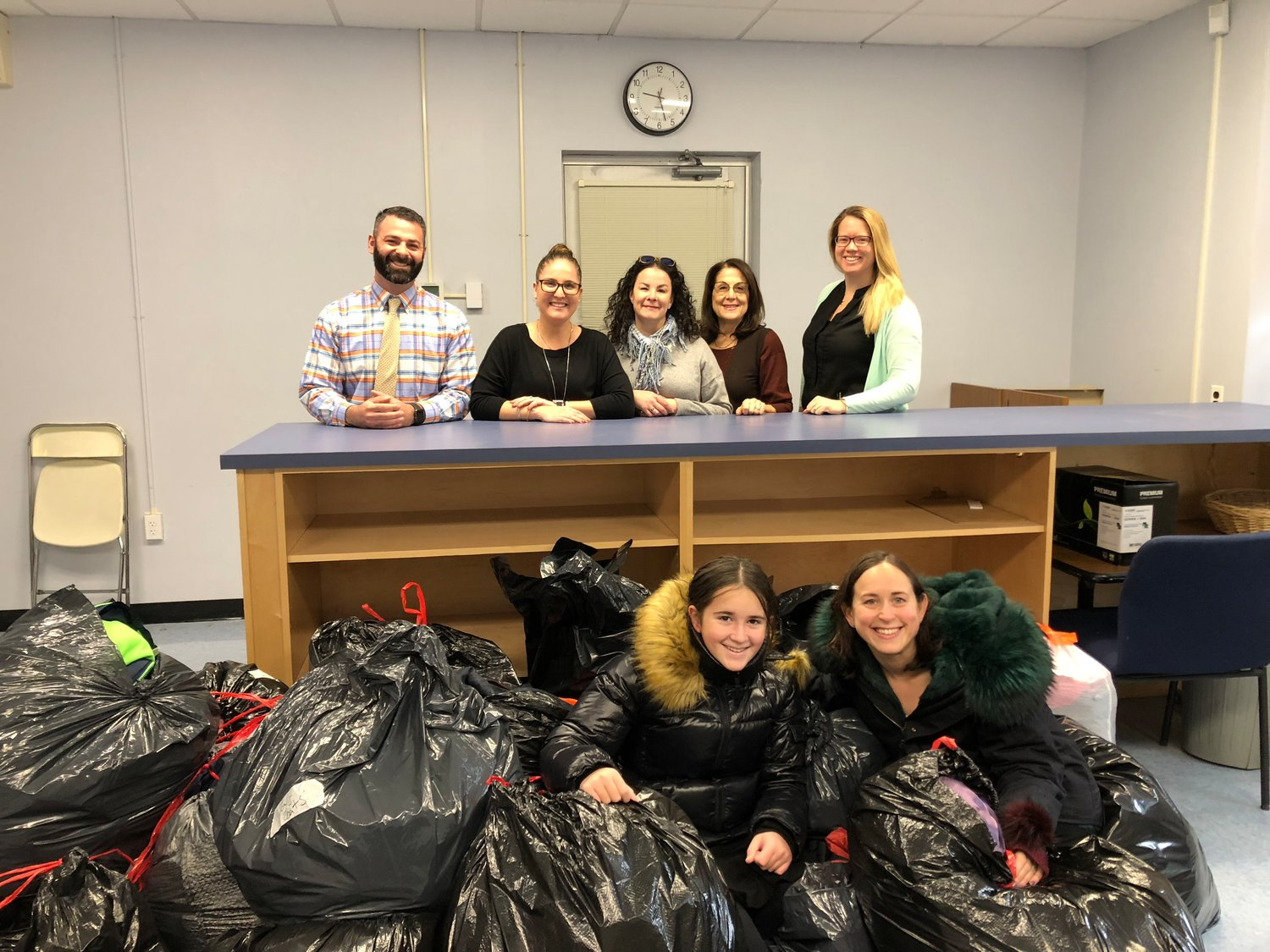 Bags filled with coats were collected and sorted at Lawrence Middle School. Standing from left assistant middle school principals Brett Kornblum and Kristin Mcloughlin, district speech pathologist Danielle Aronovitz, middle school social worker Wendy Grand and Assistant Middle School Principal Kathleen Dodd. Goldie Kuflik and her mother, Yaffa Kuflik, are among the bags.