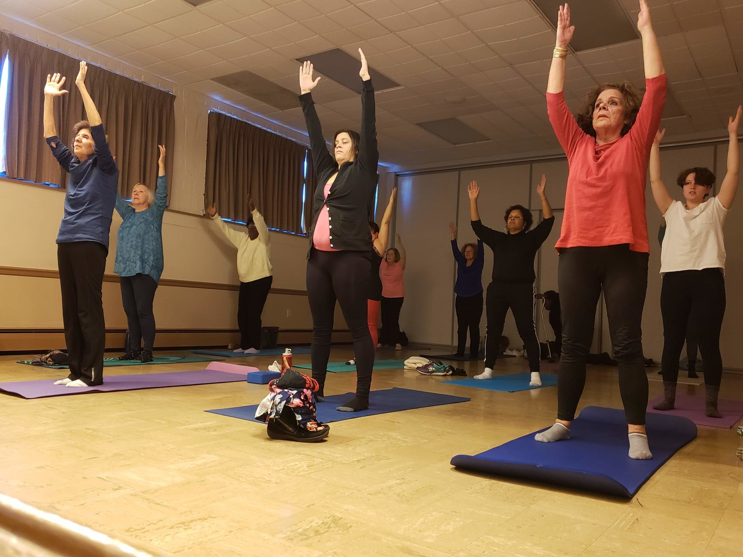 Baldwinite Helaine Savoca, Freeporter Laura Balalaos, and Lido Beach resident Marilyn Penaeene stretched at the start of the yoga class held at the Freeport Memorial on Dec. 18.