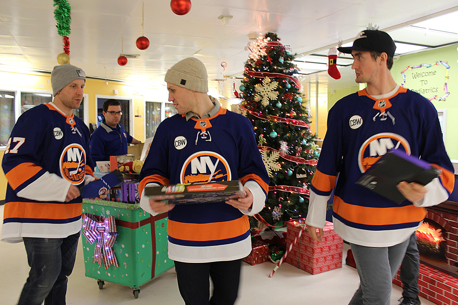 Leo Komarov, Casey Cizikas and Brock Nelson, all hockey players for the New York Islanders, spread holiday cheer throughout Nassau University Medical Center in East Meadow by giving toys and gifts to patients.