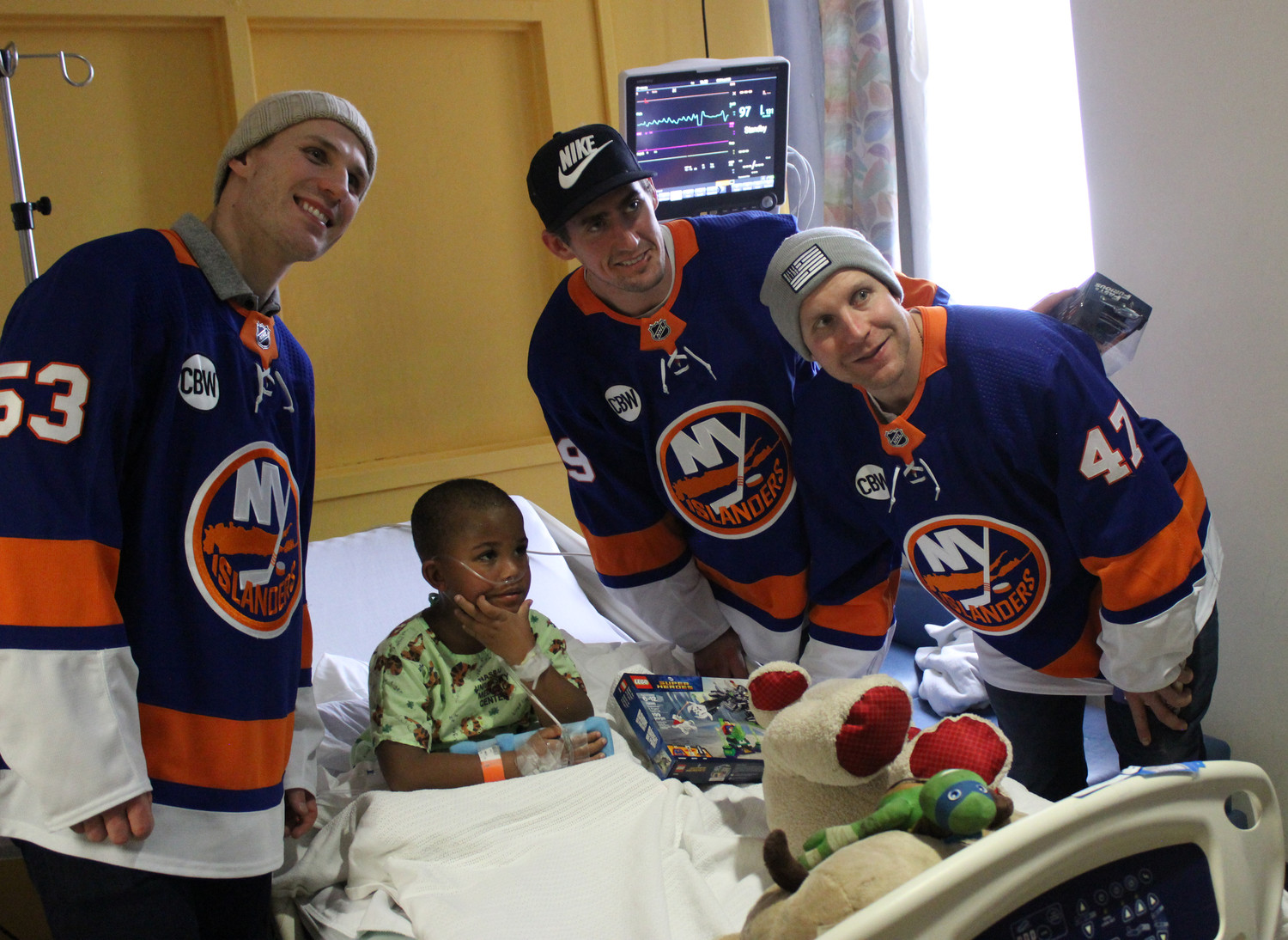 Corey Owens, 5, second-from-left, beamed when he saw Casey Cizikas, left, Leo Komarov and Brock Nelson enter his room at NUMC.